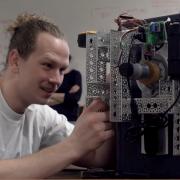 Senior Kenzy O'Neill makes an adjustment to his team's safecracking robot.