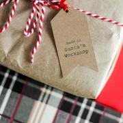 Christmas present wrapped in brown paper with festive string and handmade gift tag