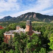 Old Main building with greenery, Flatirons behind