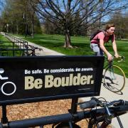 A bicyclist rides past a bike rack at the University of Colorado Boulder.
