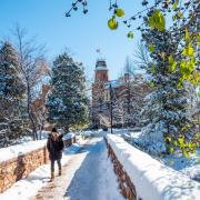 Person walking across snowy bridge with Old Main in the background