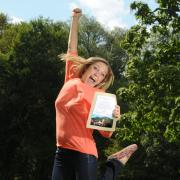 Student jumps in the air holding scholarship notification