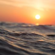 Ocean waves with orange sunset in background
