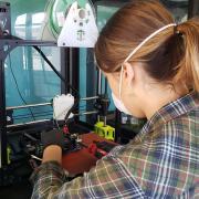 Rachel Sharpe conducts repairs on a 3D printer.