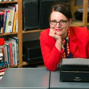 Artist Sheryl Oring, dressed in red white and blue, sits at a desk in front of her vintage typewriters.