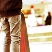 A skateboard is propped up near someone's legs, wearing jeans.