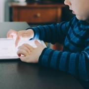 Child plays on tablet while sitting at table