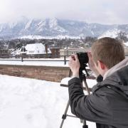 Kevin Ziznewski, a sophomore film and geography double major, snaps some frames of the snow-covered Flatirons. Photo by Patrick Campbell.