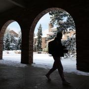 person walking on snowy campus