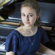 Sophia Zervas sitting in front of piano