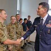 Gen. Thompson shakes hand with an ROTC cadet in fatigues