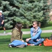 Students sit on grass at Norlin Quad