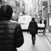 Person in hoody stalking woman on empty street