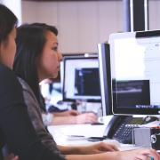 Two women work at desktop computers