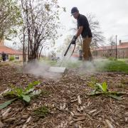 Facilities Management staff members treats weeds with steam on campus