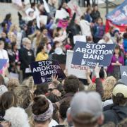 Demonstrators hold up signs at a Stop Abortion Bans rally