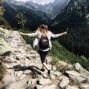 Woman frolics down rocky, mountainous path