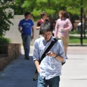 Student walking on campus, looking at smartphone