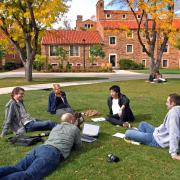 Students sit on the grass in a circle at Norlin Quad