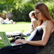 Student sits outside, leaning against tree, working on laptop