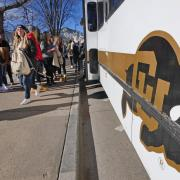 Students walk past Buff Bus