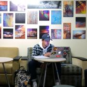 Student studying on campus with art in background