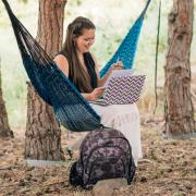 Student sits in hammock on campus while studying
