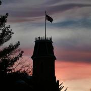 Silhouette of Old Main with sunset in the background