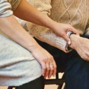 Woman rests hand on man's arm next her