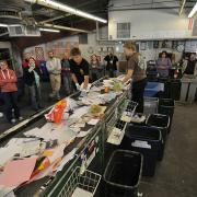 People observe the recycling sorting line during a sustainability tour