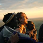 Students and locals watching the sunset in Tanzania