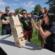 Students play a wooden stacking block game at Taste of CU.