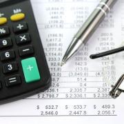 Calculator, pay stubs, pen and eye glasses