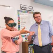 Teacher in classroom with student wearing virtual reality goggles.