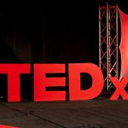 3D, red TEDx logo on stage, photo courtesy of TEDx Oakland University