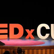 Large letters spelling TED x CU appear on a stage