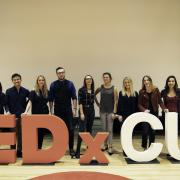 Committee executives pose for a photo in front of the TEDxCU letters
