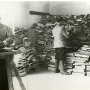 Black and white image of men looking through massive piles of books