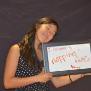 """Woman holding a sign reading """"I (de)stress by.... napping! zzzz"""