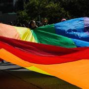 people hold large rainbow tarp outside