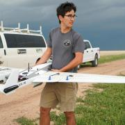 Smead Scholar Alex Hirst, a graduate researcher, helps get a drone ready for launch.