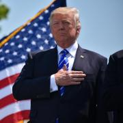 President Donald Trump placed hand over heart with flag in background
