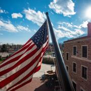 American flag flying on campus with mountains in background