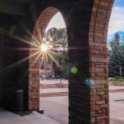 Sun peaks through pillars outside of UMC