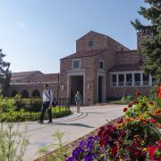 Students walking past UMC, flower beds in full bloom
