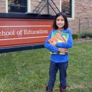 Alana Valladares poses with her books in front of the School of Education building
