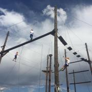 Staff members take on a ropes course as part of the University Perspectives Program