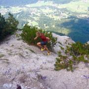 a male athlete runs uphill in mountainous terrain