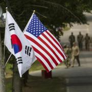 Republic of Korea and U.S. flags fly side by side, soldiers in background