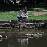 Student studying by Varsity Lake.